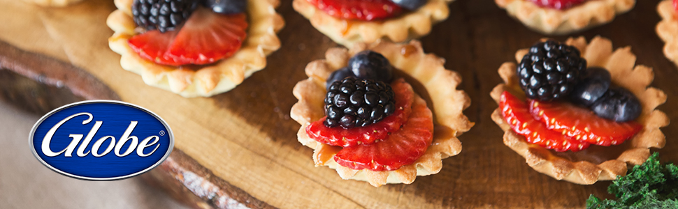 Small tartelettes with berries on wooden cutting board